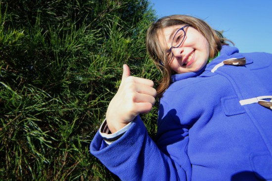 girl-christmas-tree-thumbs-up